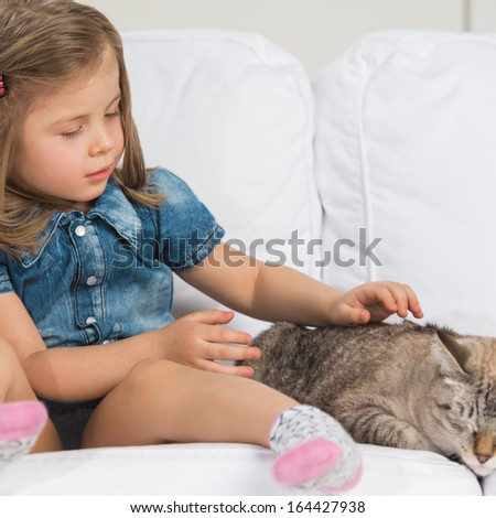 Cute little girl hugging tabby cat with love, looking at cat. - stock photo
