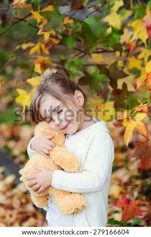 Cute little girl hugging teddy bear toy at autumn background - stock photo