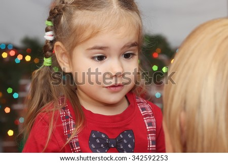 Cute little girl hugging the adult woman (back view) over blurred Christmas decorated fireplace on background, winter holiday family concept