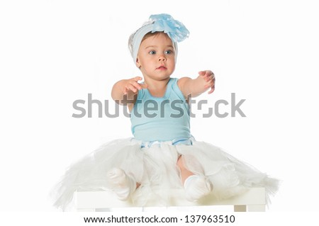Cute little girl in a ballet skirt with a blue bow on her head - stock photo