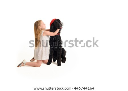 Cute little girl in a beige dress playing with her poodle and trying to put a small red round hat on it. The dog resists and sticks out his tongue. Both of them are isolated on a white background - stock photo