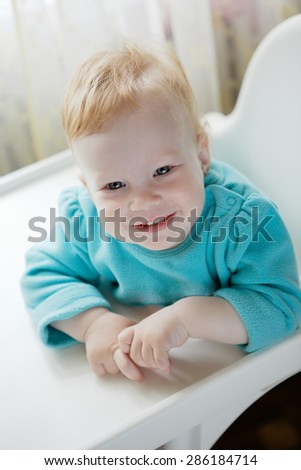 Cute little girl in a blue dress looking at the camera - stock photo