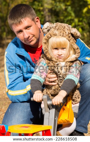 Cute little girl in a cat suit with spotted print posing in the arms of her father outdoors in the garden holding a colorful toy - stock photo