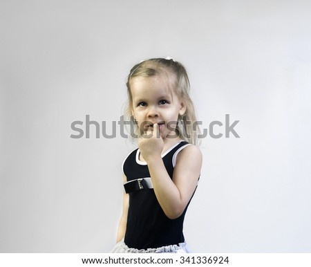 Cute little girl in a dark blue dress holding a finger in his mouth and surprised admiringly looking up, portrait in the studio - stock photo