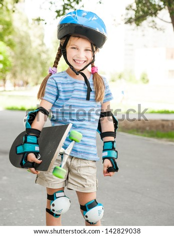 cute little girl in a helmet holding a skate - stock photo