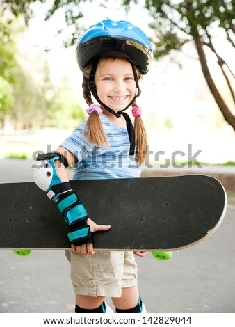 cute little girl in a helmet holding a skate in a park