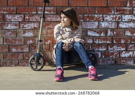 Cute little girl in a light coat and jeans sitting on a scooter in a brick wall in the city