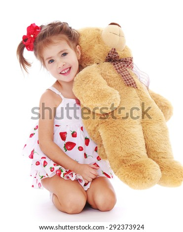 Cute little girl in a light white dress is holding on his knees a Teddy bear - isolated on white background - stock photo