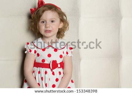 Cute little girl in a polka-dot dress with a red bow on her head