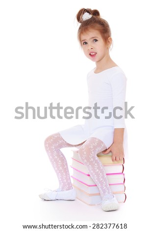 cute little girl in a white dress sitting on a pile of books.- isolated on white background - stock photo