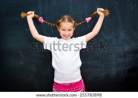 cute little girl in a white shirt against the school board raised pigtails - stock photo