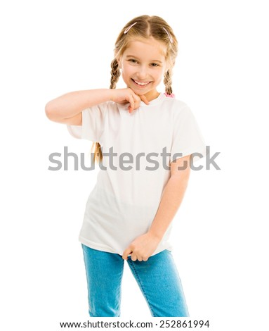 cute little girl in a white T-shirt and blue jeans on a white background shows a T-shirt on - stock photo