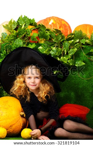 Cute little girl in a witch costume posing with pumpkins. Halloween.  - stock photo