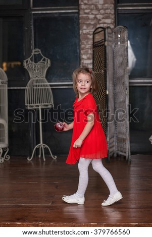 Cute little girl in about four years old in a red dress - stock photo