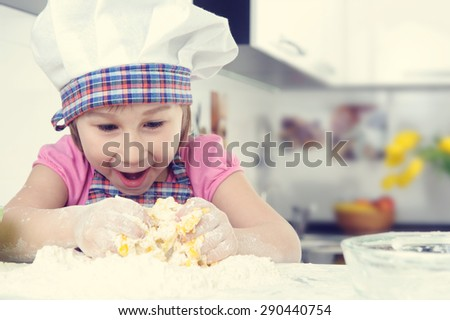 Cute little girl in apron baking cookies at home kitchen - stock photo
