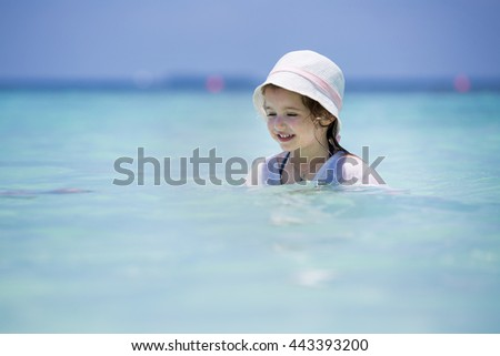Cute little girl in bathing suit playing in the clear ocean on the tropical resort beach with white sand, azure blue sea and coconut palms. Paradise Landscape background. Happy and excited child. - stock photo