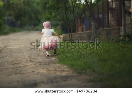 cute little girl in dress running away - stock photo