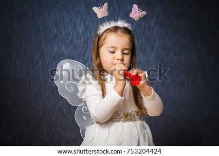 Cute little girl in fairy costume have fun and plays on red little horn on dark blue background. Studio portrait, close up.