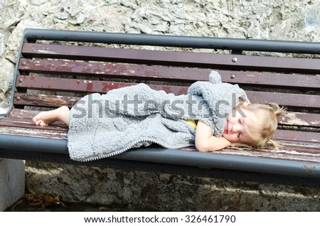Cute little girl in fur coat sleeping on the bench in park. - stock photo