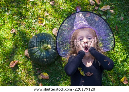 Cute little girl in Halloween which costume have fun outdoor - stock photo