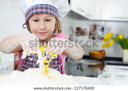 Cute little girl in hat and apron cooking cookies - stock photo