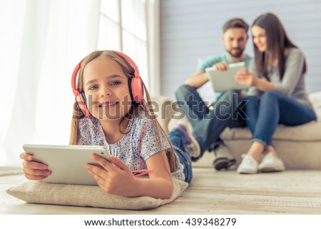 Cute little girl in headphones is using a tablet and smiling, in the background her parents are using a tablet too, sitting on sofa at home