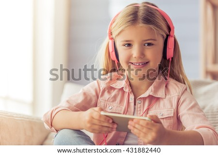 Cute little girl in headphones is using a tablet, looking at camera and smiling while sitting on the sofa at home - stock photo