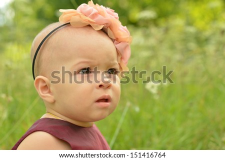 cute Little girl in park with flower on her head