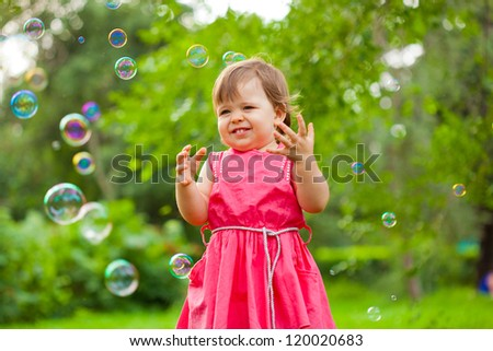 cute little girl in pink dress at park with flying soap bubbles