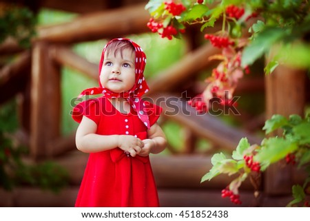 Cute little girl in red dress and head scarf standing near viburnum. Colorful photo of pretty child. - stock photo