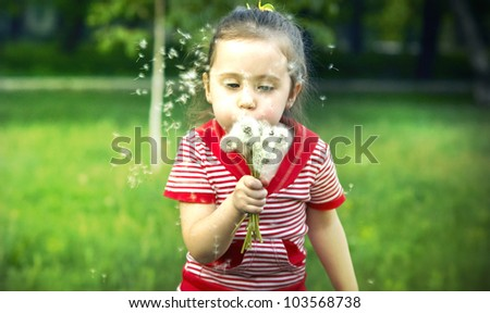 Cute little girl in red dress playing with a dandelion - stock photo