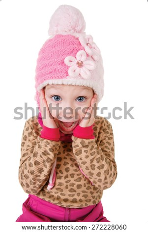 Cute little girl in red hat holding hands to face in surprise isolated on white background