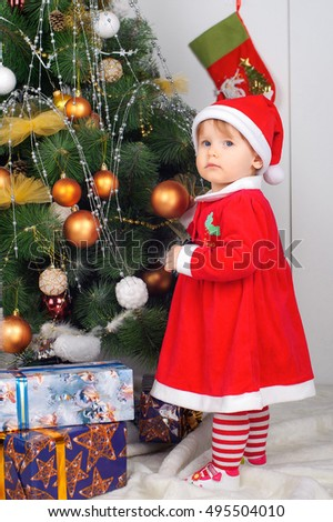 Cute little girl in Santa's suit near a Christmas tree