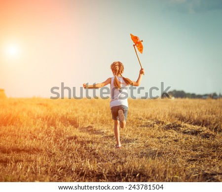 cute little girl in summer day holds windmill in hand - stock photo