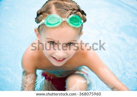 Cute little girl in swimming pool. Summer outdoor. - stock photo