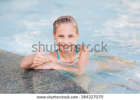 Cute little girl in swimming pool with thumb up
