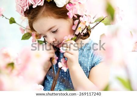 Cute little girl in the flower garden - stock photo