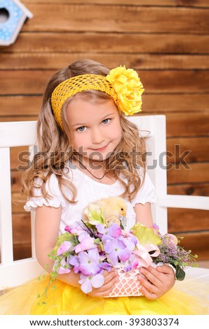 cute little girl in white and yellow with wavy hair with garland holding basket with flowers and alive chicken on brown wooden wall background - stock photo