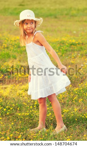 Cute little girl in white dress walking on the meadow on beautiful spring day. - stock photo