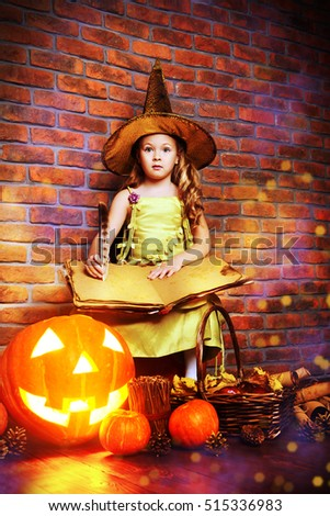 Cute little girl in witch costume with pumpkins. Halloween. Studio shot.