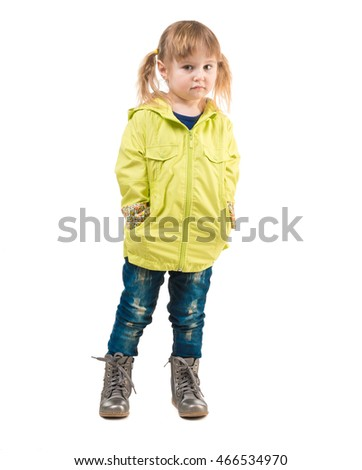cute little girl in yellow coat and hands in pockets isolated on white background