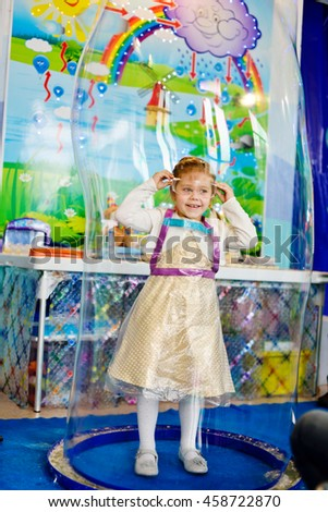 cute little girl inside of the soap bubble  on the birthday party