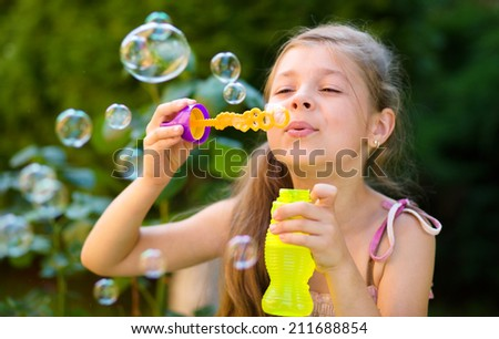 Cute little girl is blowing a soap bubbles, outdoor shoot - stock photo