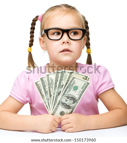 Cute little girl is counting dollars, isolated over white - stock photo