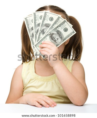 Cute little girl is covering her face with dollars, isolated over white