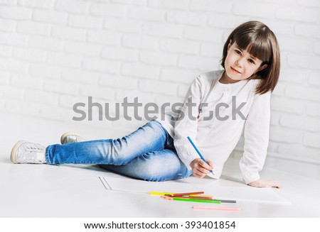 Cute little girl is drawing on a floor - stock photo