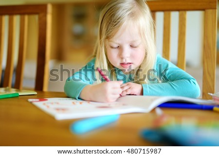 Cute little girl is drawing with colorful markers in preschool