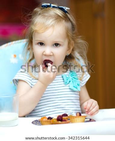 Cute little girl is eating cake - stock photo
