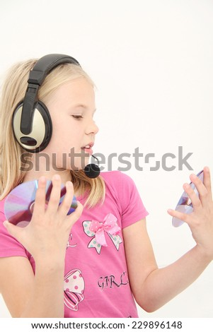 Cute little girl is enjoying music using headphones - stock photo