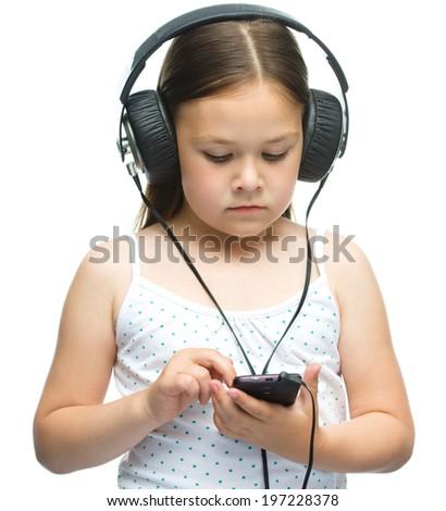 Cute little girl is enjoying music using headphones, isolated over white - stock photo